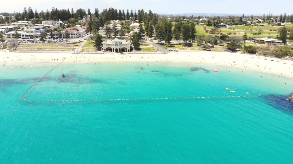 A drone image of the eco shark barrier at Cottesloe Beach, with the iconic Indiana Tea Rooms in the background.